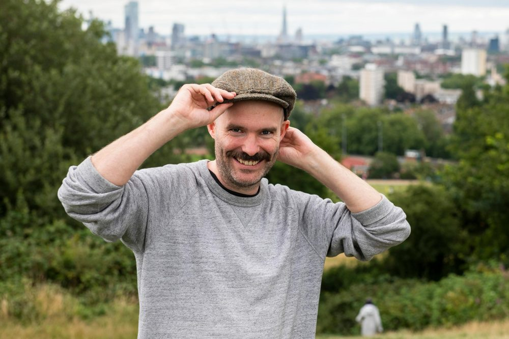 dating photo london. Man poses for a photograph with city background